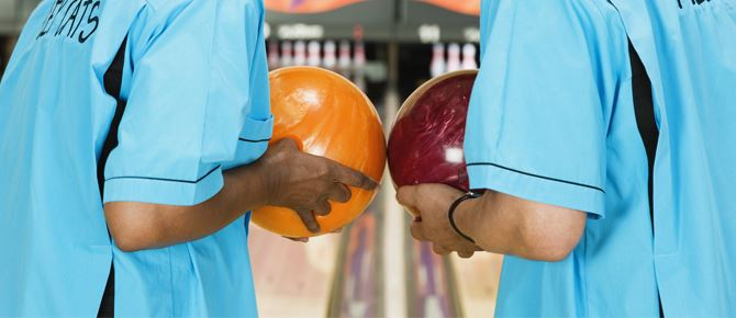 Two people holding bowling balls
