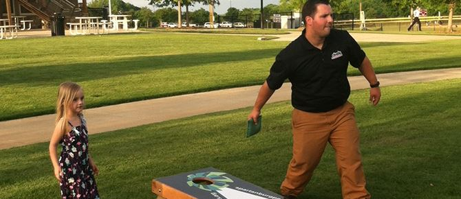 Man and young girl playing corn hole