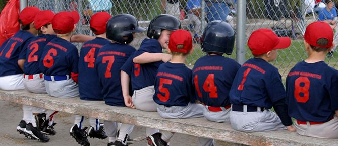 Young baseball players sitting down